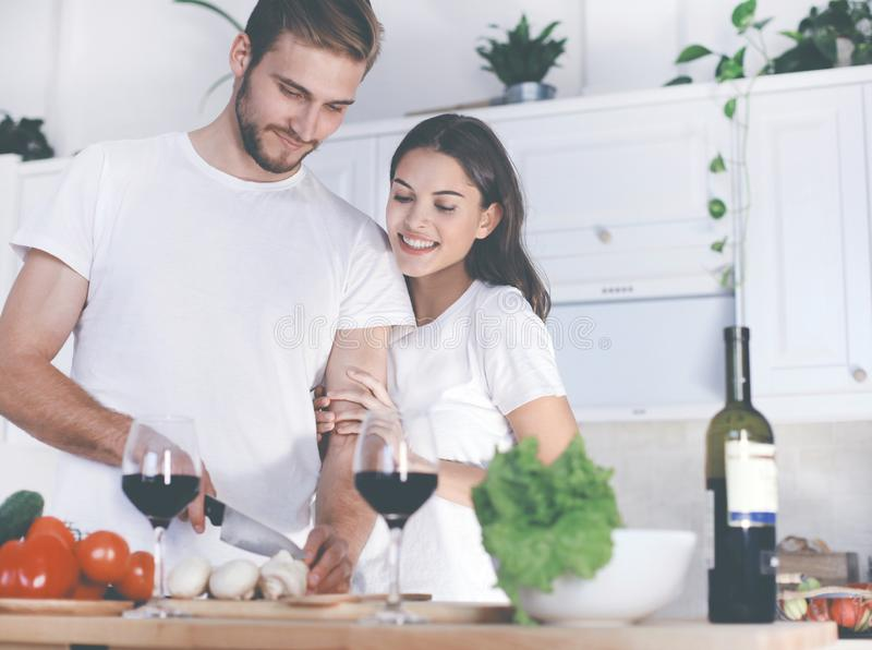 Beautiful young couple preparing a healthy meal together while spending free time at home. stock photography