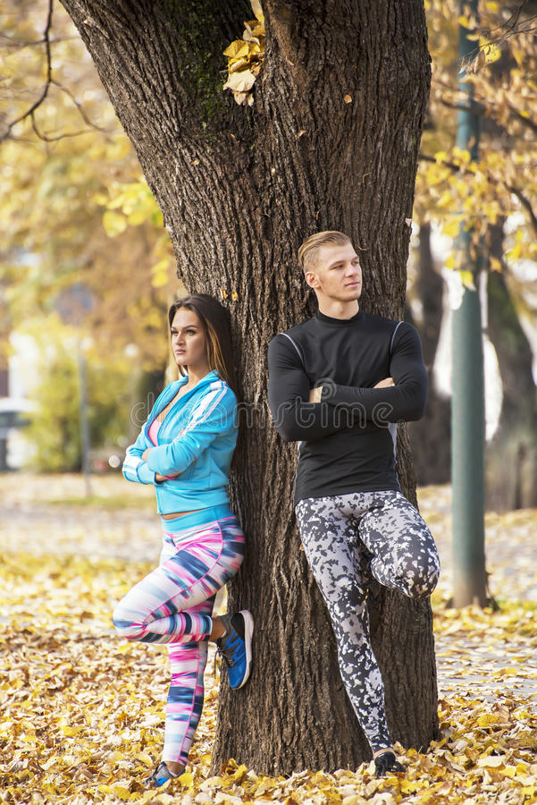 Beautiful young couple recumbent to tree together in the park. Autumn environment royalty free stock images