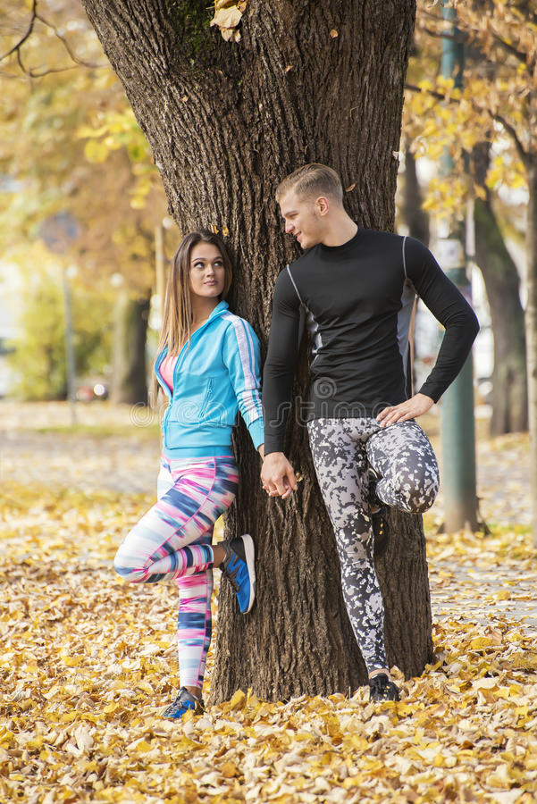 Beautiful young couple recumbent to tree together in the park. Autumn environment stock image