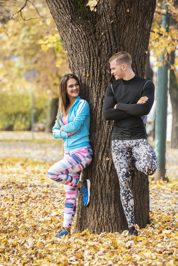 Beautiful young couple recumbent to tree together in the park. Autumn environment stock photos