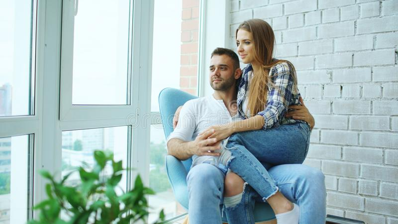 Beautiful young couple relax sitting on chair and enjoying view from balcony of new loft apartment royalty free stock images