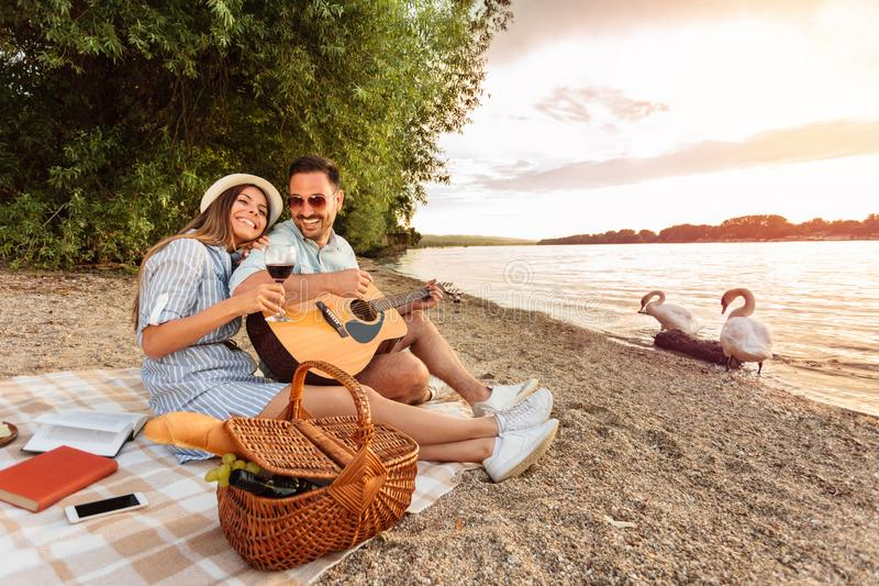 Man is playing guitar and his girlfriend is resting her head on his shoulder. Sunset over water in the background royalty free stock photo