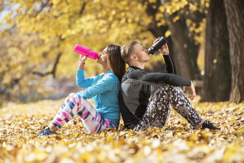 Beautiful young couple resting and rehydration after successful training in the park. Autumn environment royalty free stock images