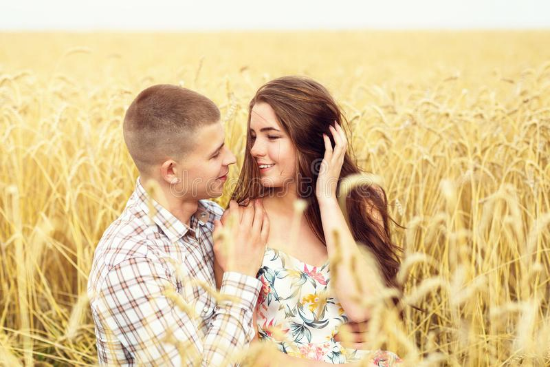 Beautiful young couple is resting on a wheat field. A girl in love and her boyfriend are hugging. Family outdoor recreation royalty free stock images