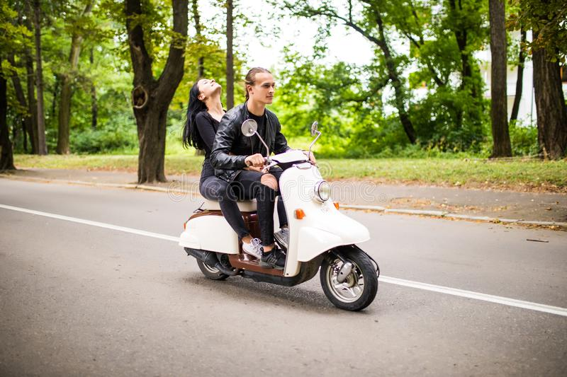 Beautiful young couple riding scooter together, woman hugging her boyfriend. Side view on speed. royalty free stock images