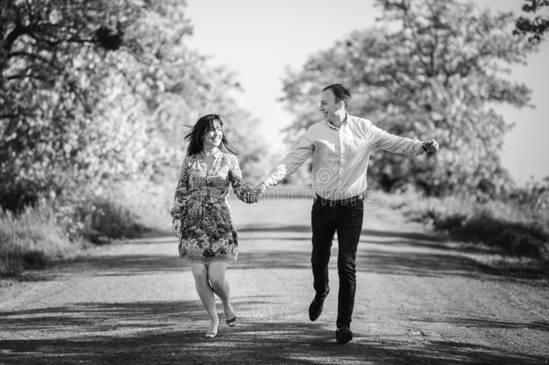 Beautiful young couple running holding hands in spring meadow. Happy stylish family having fun on road at field trees. Romantic stock images
