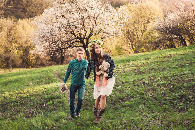 Beautiful young couple runs on path in blossom garden. royalty free stock photography