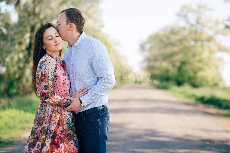 Beautiful young couple sensual hugging and kissing on road in sunshine among spring field and trees. Happy family in love stock images
