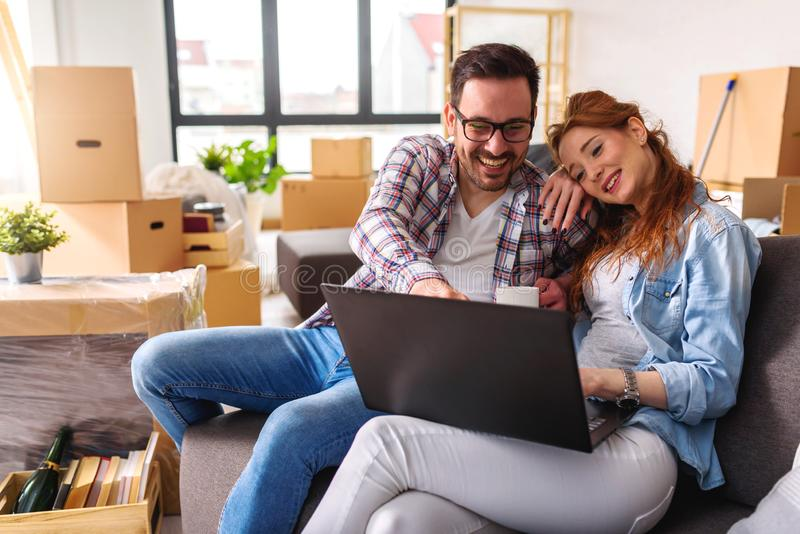 Beautiful young couple shopping on-line using a laptop computer and smiling while sitting in their new apartment after move royalty free stock images