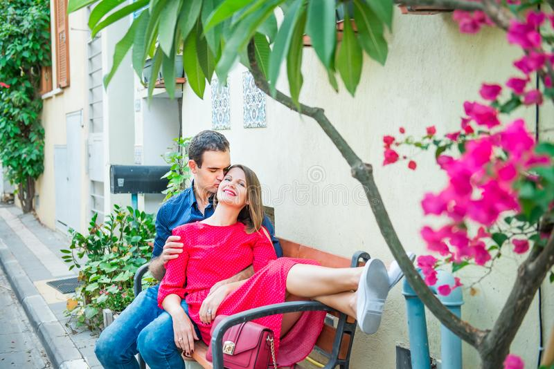 Beautiful young couple sitting on the bench on mediterranean city street with blooming trees. Love, dating, romance, joy and happi royalty free stock photos