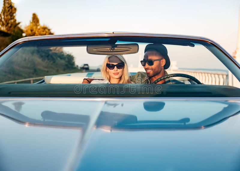 Beautiful young couple sitting and driving cabriolet royalty free stock image