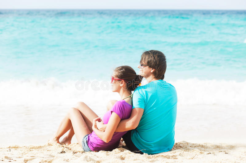 Beautiful young couple sitting and having fun on beach royalty free stock photography