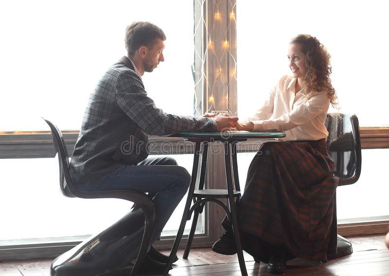 Beautiful young couple sitting at a table in a cozy cafe stock images