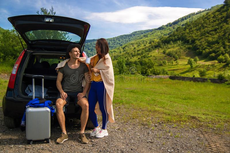 Beautiful young couple sitting in the trunk of a car and admire the beautiful scenery on the mountain. Young couple sitting on the back of a off road vehicle stock photos