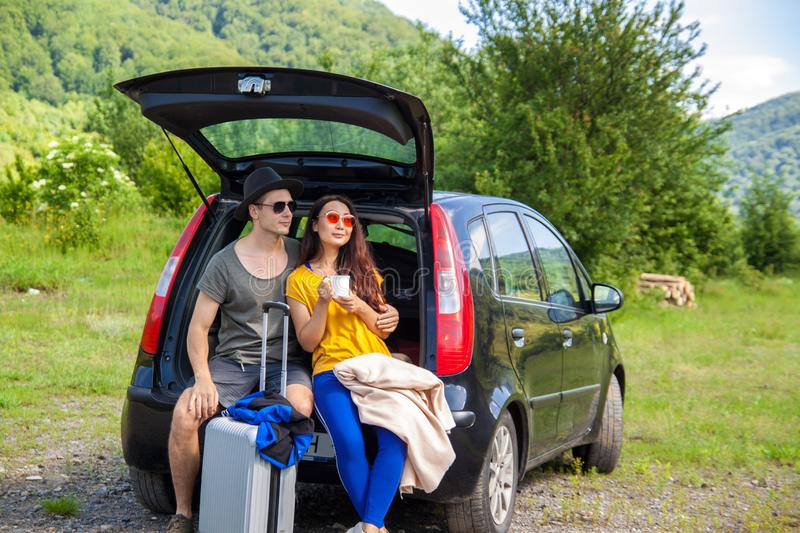 Beautiful young couple sitting in the trunk of a car and admire the beautiful scenery on the mountain. Young couple sitting on the back of a off road vehicle stock image