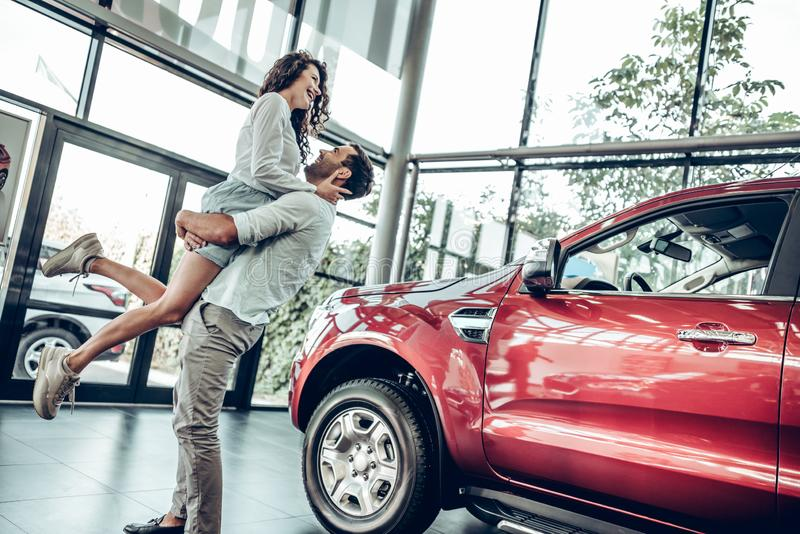 Beautiful young couple is smiling while buying a car in a motor show. Man is holding women in his arms. Bottom view royalty free stock image