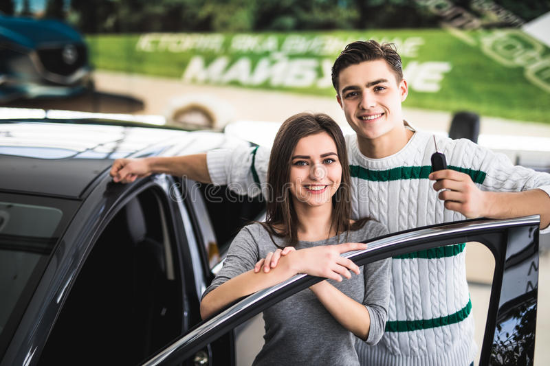 Beautiful young couple is smiling and looking at camera while leaning on their new car in a motor show. Man is holding car keys royalty free stock images