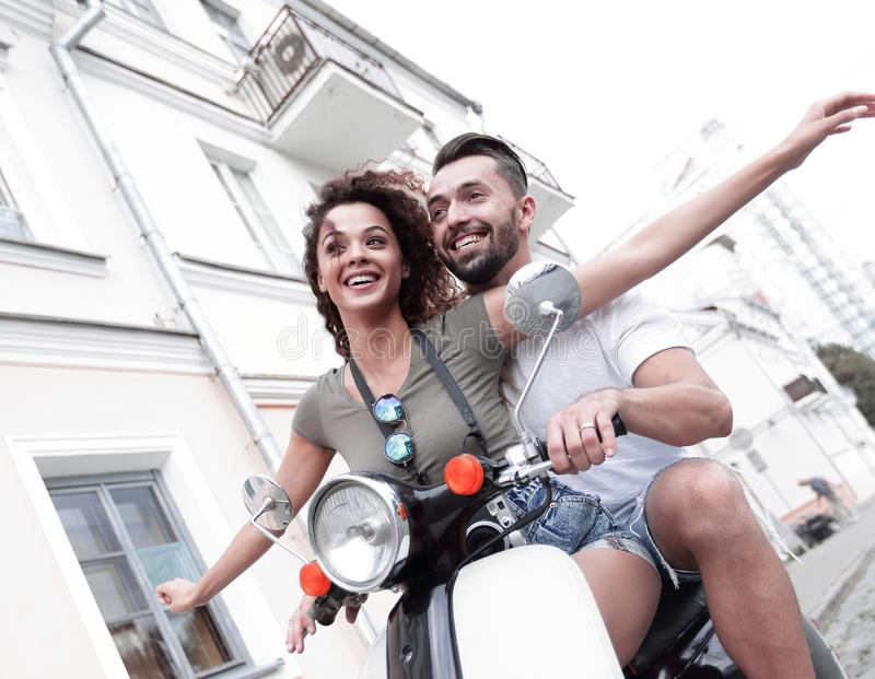 Beautiful young couple is smiling while riding a scooter stock image