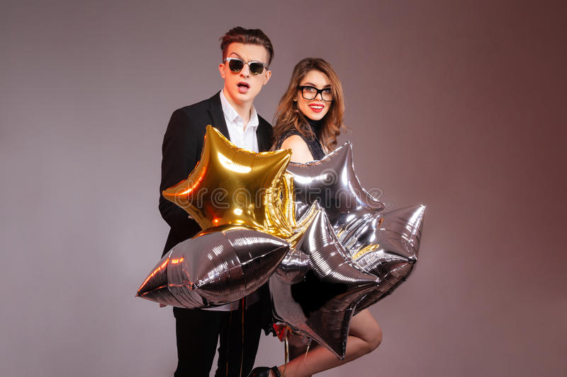 Beautiful young couple standing and holding star shaped balloons royalty free stock photos