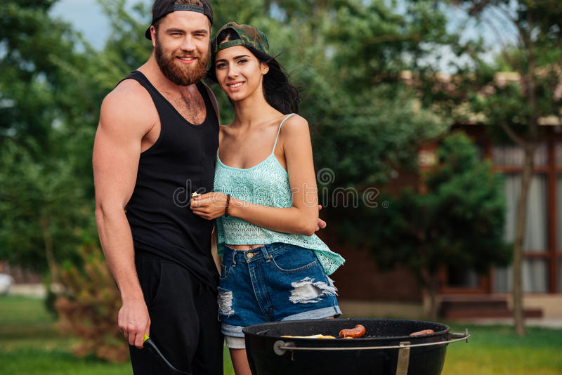 Beautiful young couple standing near barbeque grill outdoors stock photo