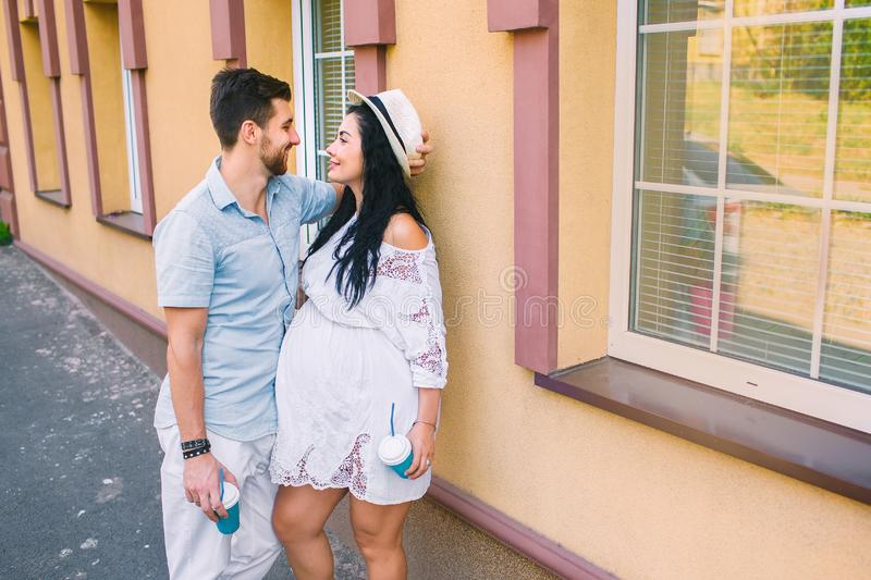 A beautiful young couple is standing near the building, the girl is pregnant, the family is drinking coffee, tea, the sweethearts stock photo