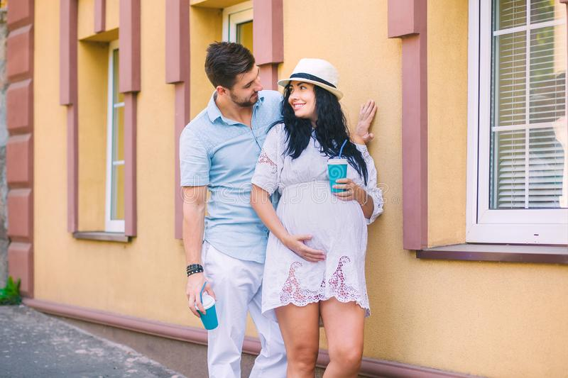 A beautiful young couple is standing near the building, the girl is pregnant, the family is drinking coffee, tea, the sweethearts royalty free stock photo