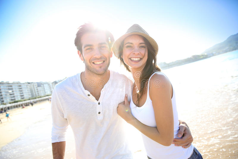 Beautiful young couple in sunlight on the beach royalty free stock photo