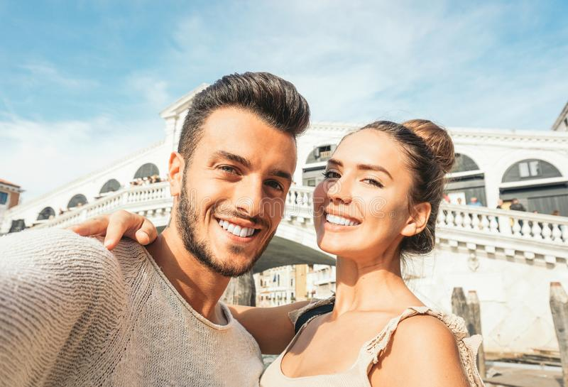 Beautiful young couple taking a selfie enjoying the time on their trip to Venice - Boyfriend and girlfriend taking a picture stock photography