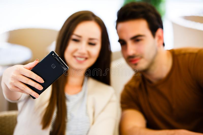 Beautiful young couple taking selfie while sitting at cafe stock photo