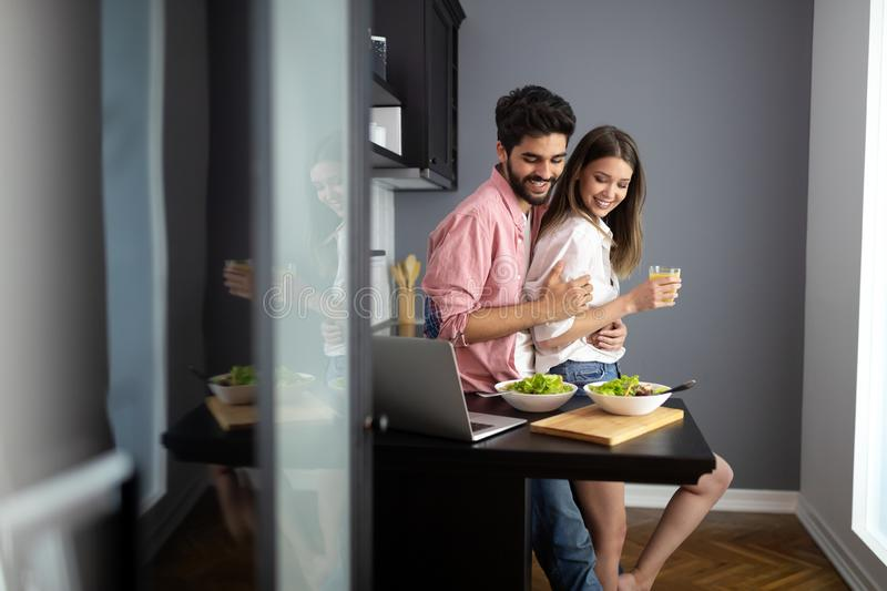 Oung couple is talking and smiling while cooking healthy food in kitchen at home stock photography