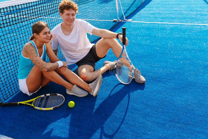 Beautiful young couple of tennis players resting royalty free stock image
