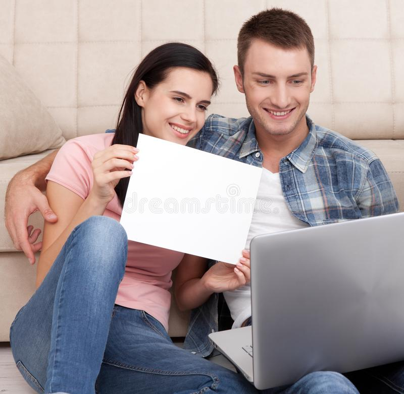 Beautiful young couple using laptop communicates in video chat. A woman is smiling and showing blank piece of paper. stock photo