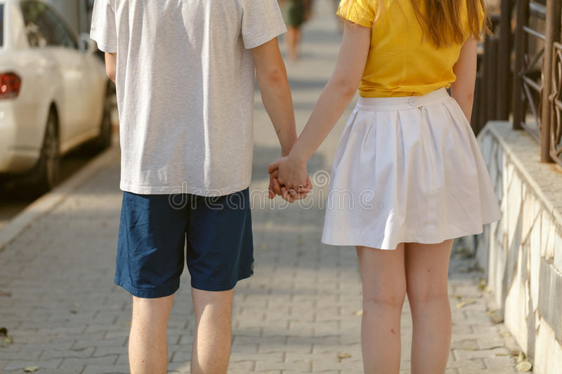 Beautiful Young couple walk hand in hand on the road royalty free stock photo