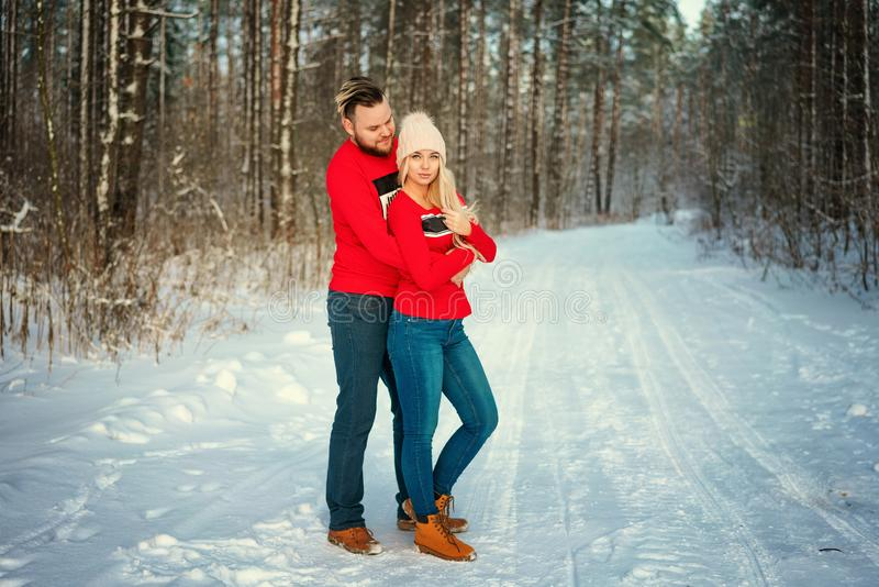Beautiful young couple in winter in the woods, hug, happy romance.  stock photography