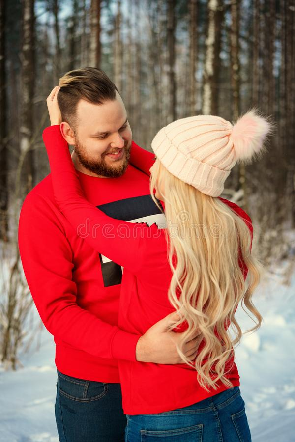 Beautiful young couple in winter in the woods, hug, happy romance stock photos