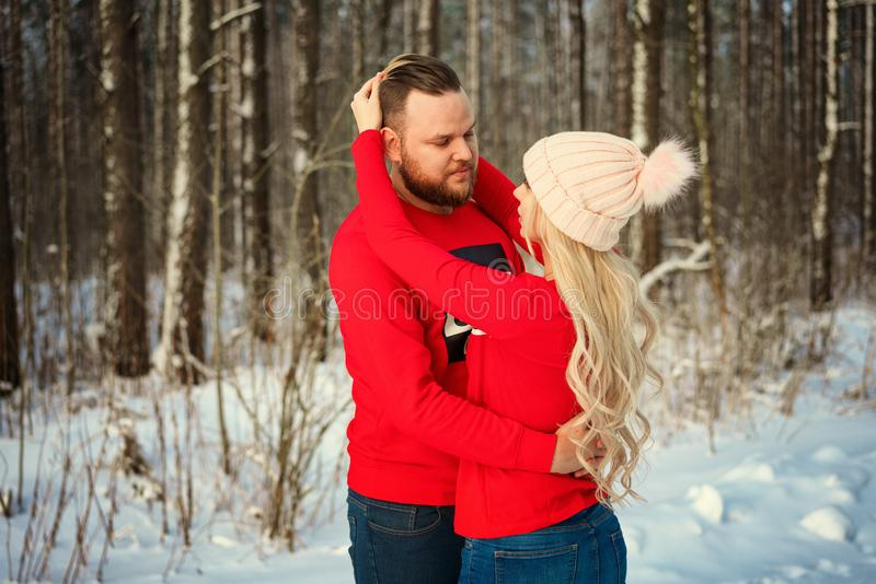 Beautiful young couple in winter in the woods, hug, happy romance royalty free stock photos