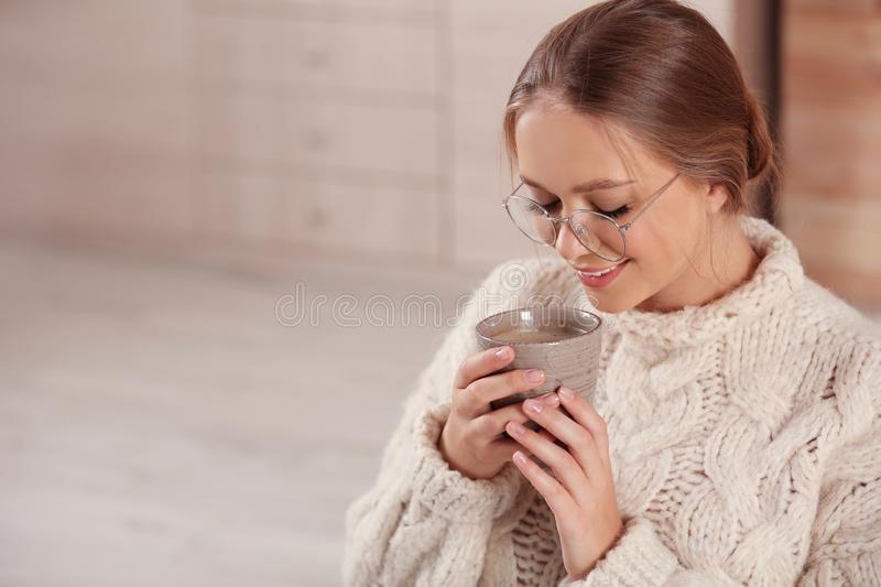 Beautiful young  with cup of hot drink at home, space for text. Winter atmosphere. Beautiful young woman with cup of hot drink at home, space for text. Winter royalty free stock image