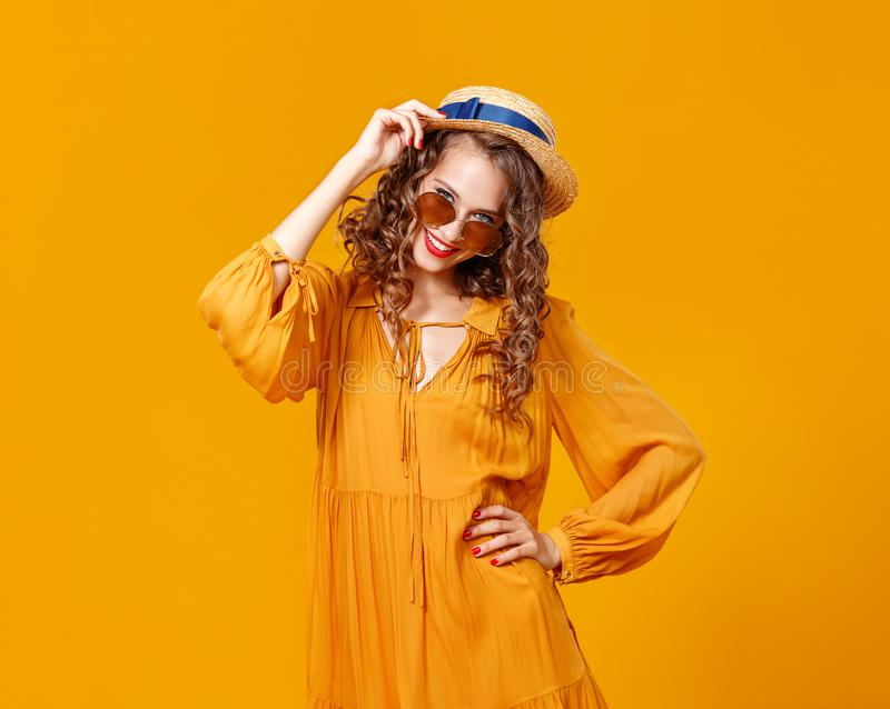Beautiful young curly woman in summer hat and sunglasses on   yellow background royalty free stock photos