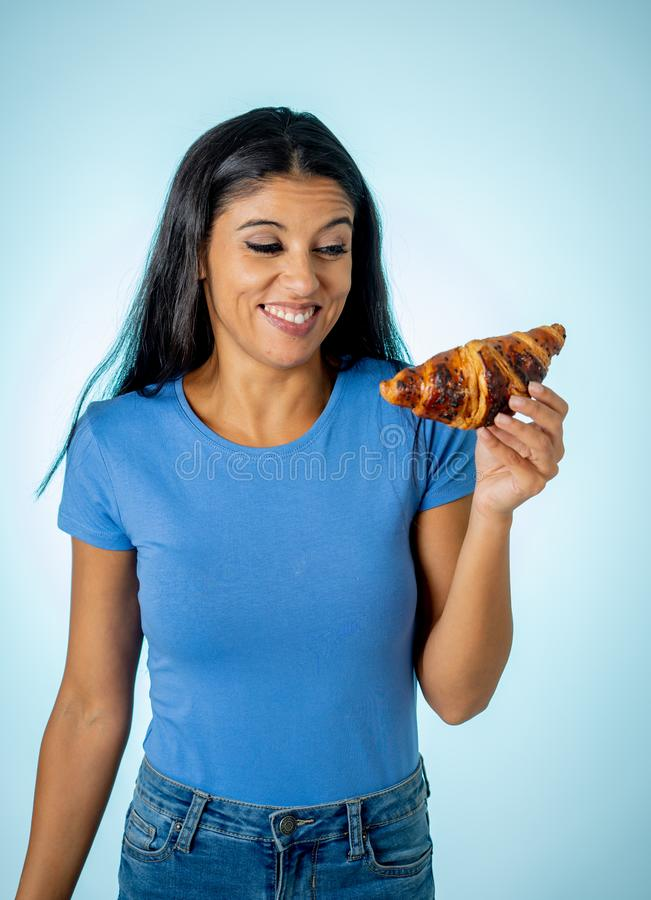 Beautiful young cute and happy latin woman in casual clothes holding big delicious chocolate croissant looking with temptation. Thinking if ignoring diet and royalty free stock photos