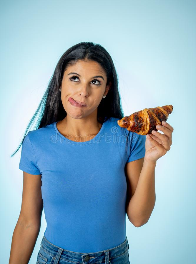 Beautiful young cute and happy latin woman in casual clothes holding big delicious chocolate croissant looking with temptation. Thinking if ignoring diet and royalty free stock images