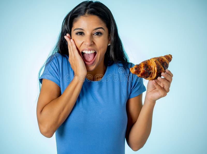 Beautiful young cute and happy latin woman in casual clothes holding big delicious chocolate croissant looking with temptation royalty free stock images