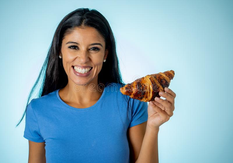 Beautiful young cute and happy latin woman in casual clothes holding big delicious chocolate croissant looking with temptation stock images
