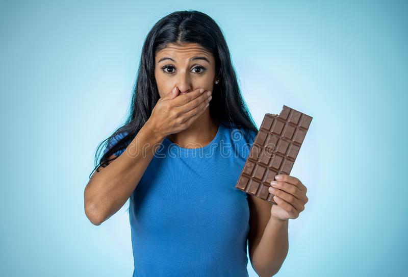 Beautiful young cute and happy latin woman in casual clothes holding big delicious chocolate tablet looking with temptation stock images