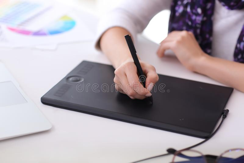 Beautiful young designer working in office stock images
