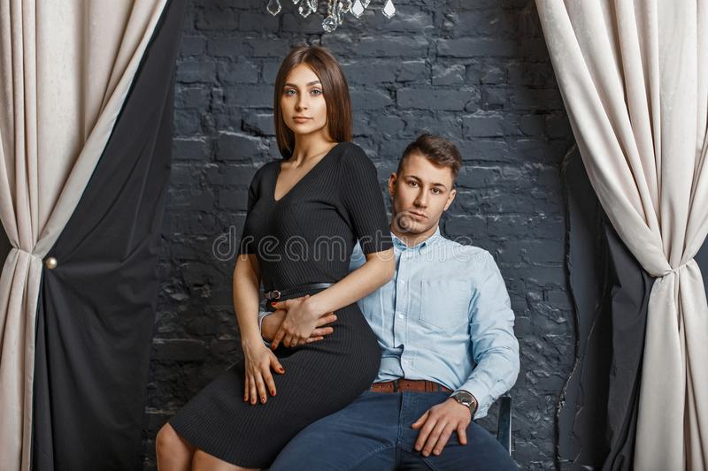 Beautiful young elegant couple in stylish clothes sitting. Near a brick wall royalty free stock image