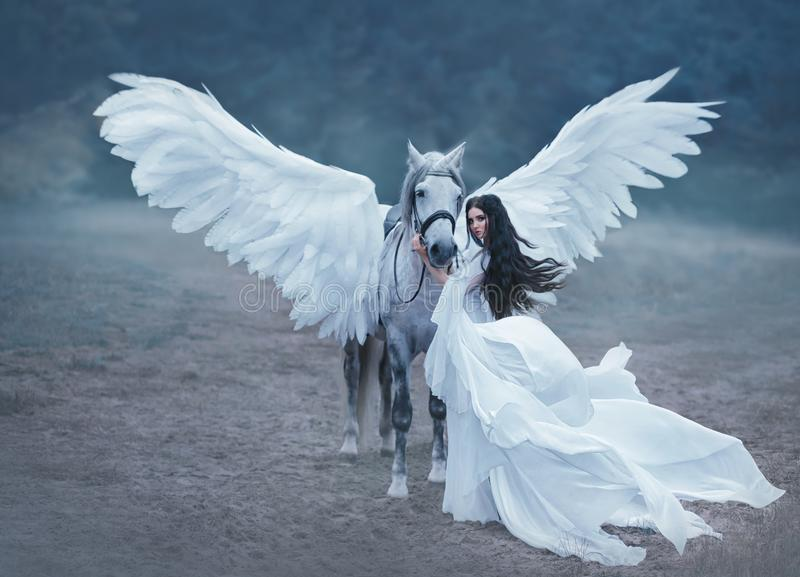 Beautiful, young elf, walking with a unicorn. She is wearing an incredible light, white dress. Art hotography stock photos