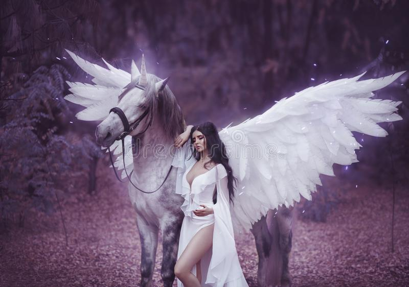 Beautiful, young elf, walking with a unicorn. She is wearing an incredible light, white dress. Art hotography. Beautiful, young elf, walking with a unicorn. She royalty free stock photography