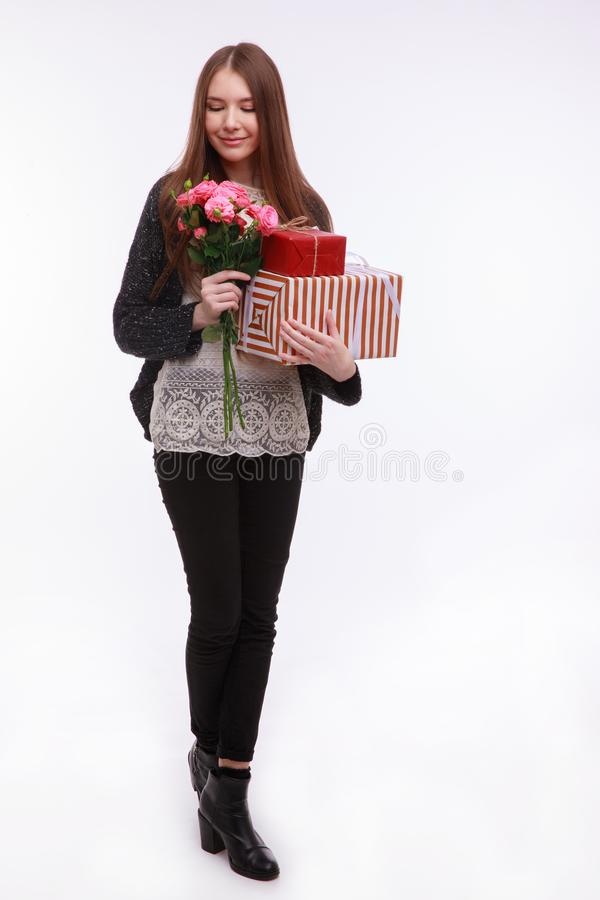 Beautiful young girl, holds gift boxes and a bouquet of flowers and a cute smile. Isolated on white. stock images