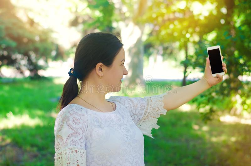 Beautiful young European girl brunette takes a picture of herself and makes selfie in the city park. people, lifestyle, walking in royalty free stock image