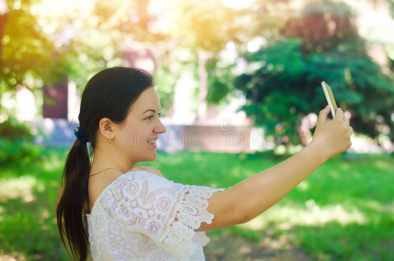 Beautiful young European girl brunette takes a picture of herself and makes selfie in the city park. people, lifestyle, walking in royalty free stock photo
